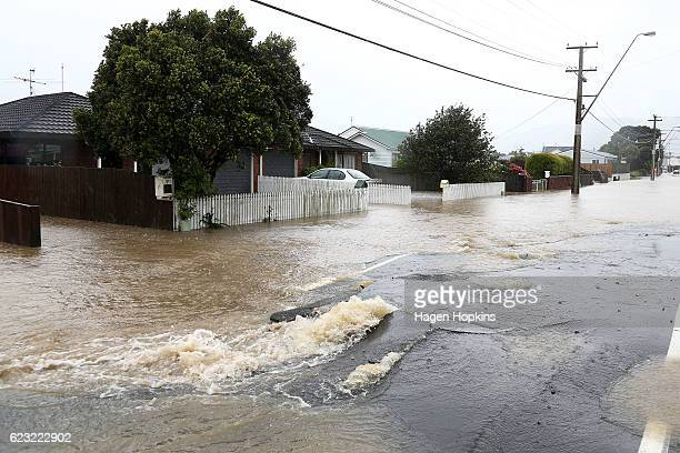 Flood water flows through cracks in the road surface on Udy Street Petone after a bout of severe weather on November 15 2016 in Wellington New...