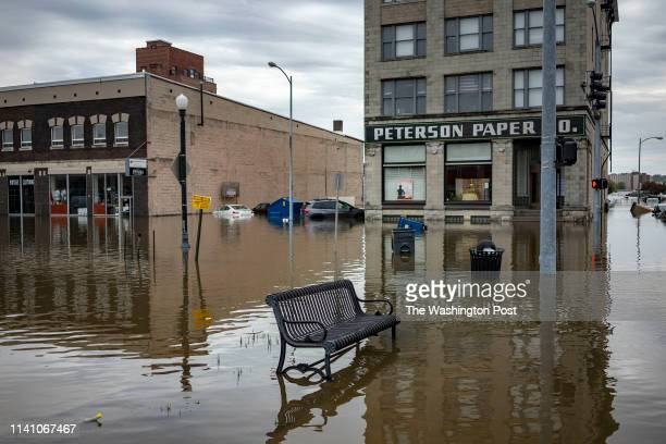 Flood water surround a bench near the main breach in the Mississippi River in Davenport Iowa on Friday May 3 2018