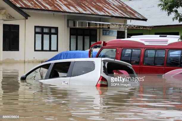 Flood water surrounds a car in a residential area in Aceh Utara district Aceh province At least one person died and thousands of homes were inundated...