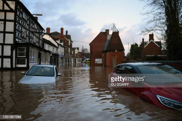 Flood water surrounds abandoned cars left in a flooded street in Tenbury Wells after the River Teme burst its banks in western England on February 16...