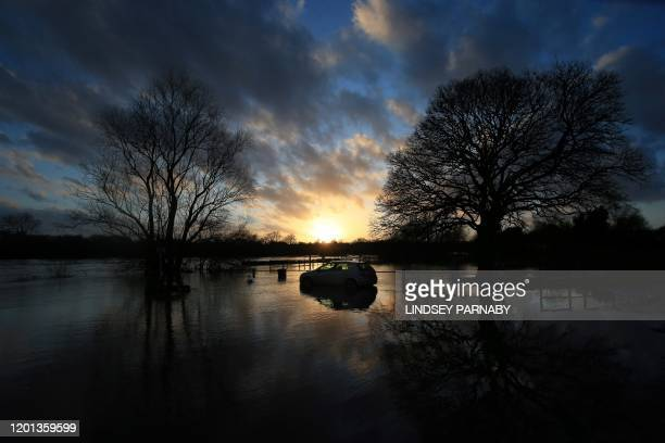 TOPSHOT Flood water surrounds an car abandoned in a car park after the River Trent burst its banks in Gunthorpe Nottinghamshire in central England on...