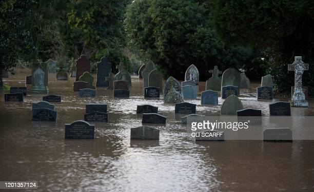 TOPSHOT Flood water surrounds grave stones in a graveyard in Tenbury Wells after the River Teme burst its banks in western England on February 16...