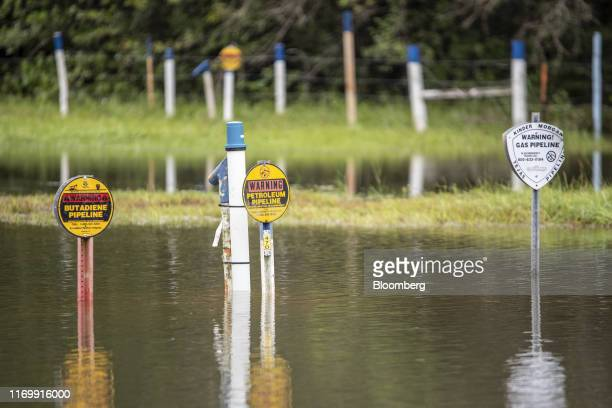 Flood water surrounds signs marking pipelines on a highway following Tropical Storm Imelda in Fannett Texas US on Friday Sept 20 2019 The remnants of...