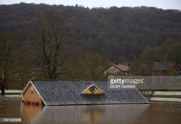Flood water surrounds the bowling club after the River Taff burst its banks in Taffs Wells, north of Cardiff in south Wales on February 16 after...