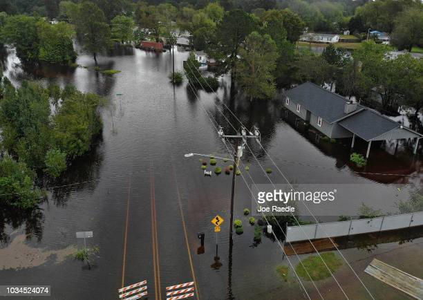 Flood waters from Hurricane Florence surround a house and flow along the street on September 16 2018 in Fayetteville North Carolina Rain continues to...