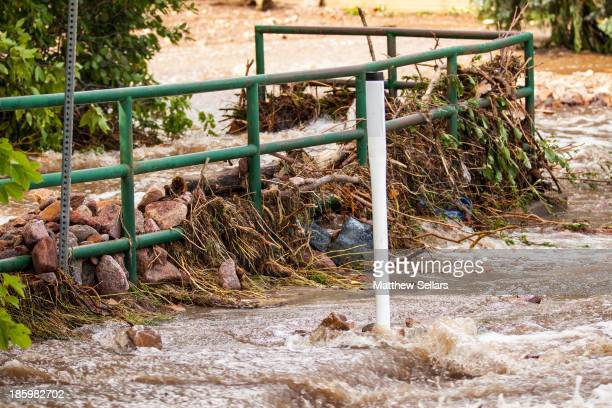 CONTENT] Flood waters mash debris against a railing as it breaches the creek and floods down 7th street in Boulder Colorado