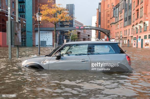 Flood waters surround a car parked at Hamburg's Fish Market district on October 29, 2017 as a storm hit many parts of Germany. At least three people...