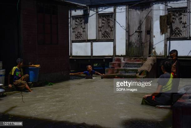 Flood-affected family stand outside their flooded house. The flood situation is worsening in Munshiganj. Due to the heavy rain, the water level of...