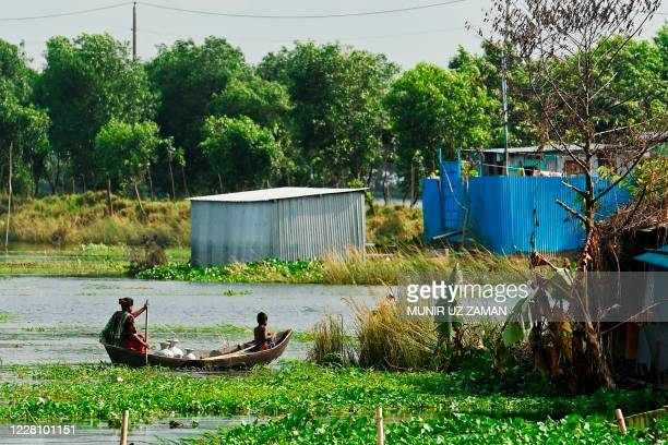 Flood-affected residents ride on a boat through a flooded village in Savar on August 19, 2020. - The death toll from the torrential monsoon rains...