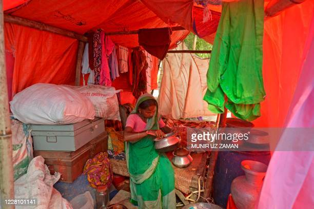 Flood-affected villager takes shelter under a temporary tent built on a street after her house was flooded in Savar on August 19, 2020. - The death...