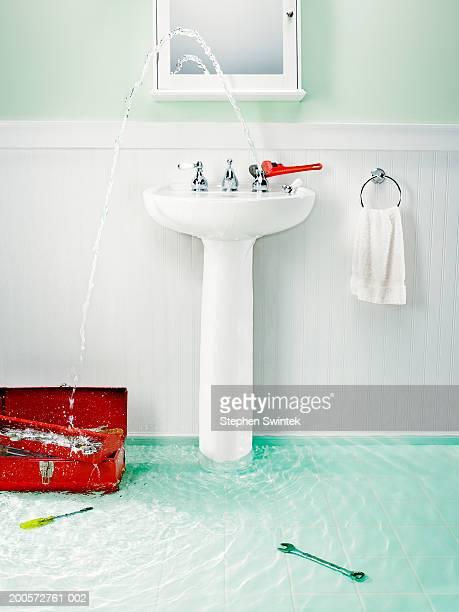 Flooded bathroom with plumbing tools