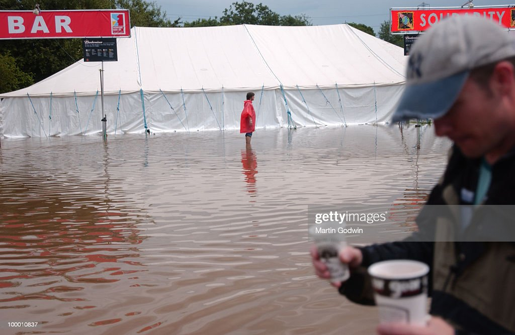 Flooded beer tent with man carrying beers through flood at Glastonbury, 24th June 2005.