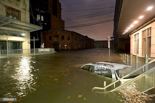 flooded car on an urban street - flooding stock photos and pictures