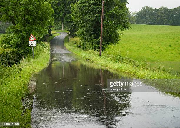 flooded country road - flooding stock photos and pictures