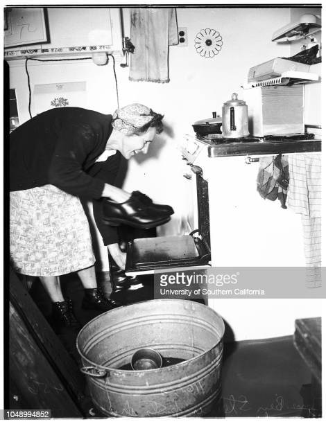 Flooded homes in Artesia area, 16 January 1952. Mr Ben Steiner, trying to bail out front room;Mrs Ben Steiner, putting husband's shoes in oven above...