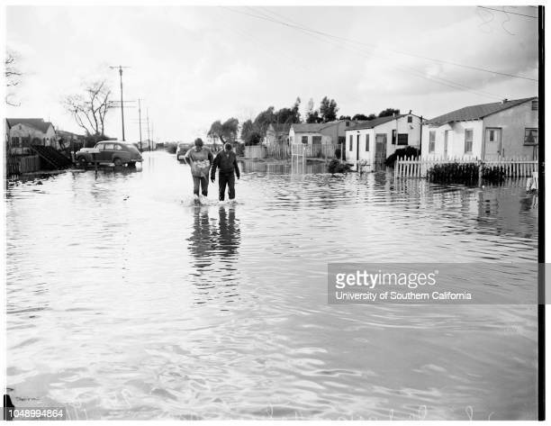 Flooded homes in Artesia area 16 January 1952 Mr Ben Steiner trying to bail out front roomMrs Ben Steiner putting husband's shoes in oven above...