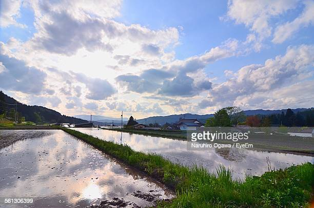 Flooded Rice Paddy By House Against Cloudy Sky