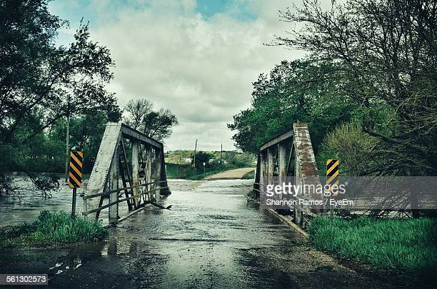 flooded river and bridge against cloudy sky - nebraska flooding stock photos and pictures