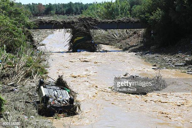 Flooded river is seen with a wrecked car in it. Excessive rainfall in the Greek city of Kalamata has the result of damage in buildings and in cars,...