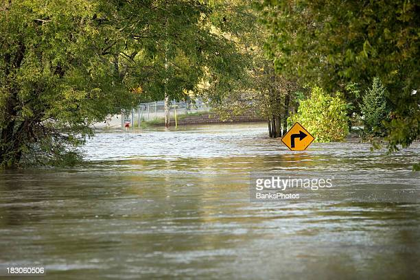 flooded river over a city street - flooding stock photos and pictures