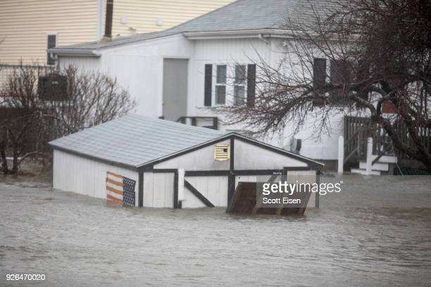 A flooded shed and home due to a strong coastal storm are seen on March 2 2018 in Quincy Massachusetts A nor'easter hit the east coast on Friday...