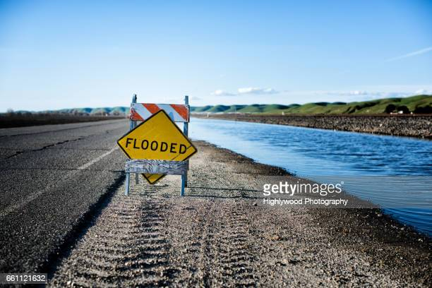 flooded sign and road - highlywood stock pictures, royalty-free photos & images