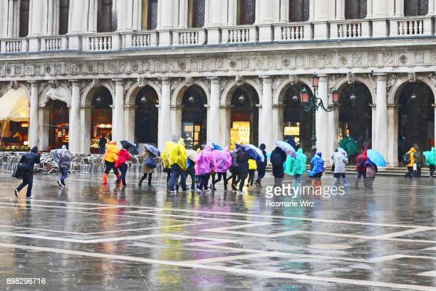 Flooded St. Mark's Square in Venice, tourist crowd running