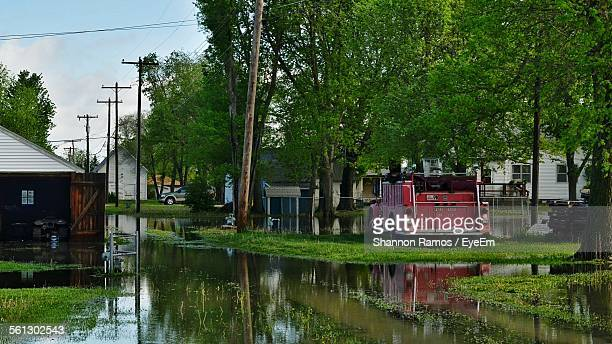 flooded streets by buildings and trees - nebraska flooding stock photos and pictures