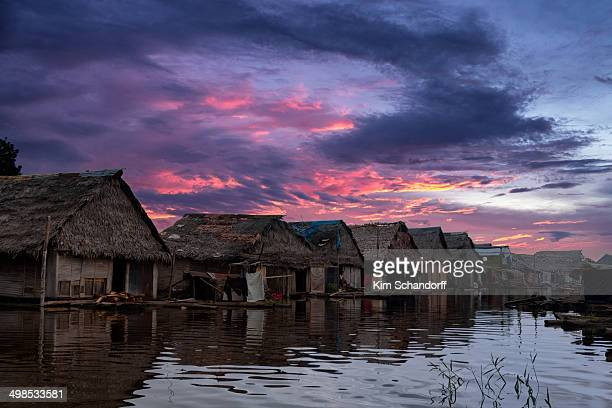 Flooded village with houses on poles in the Peruvian jungle. Sunset with reflections of the houses in the river.