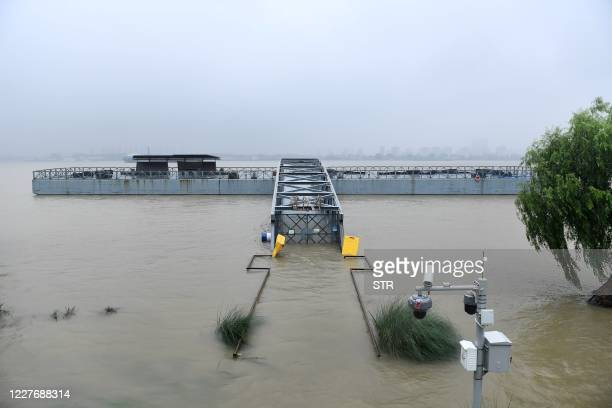 Flooded walkway is seen on the bank of the Yangtze river in Nanjing, in China's eastern Jiangsu province on July 19, 2020. - Vast swathes of China...