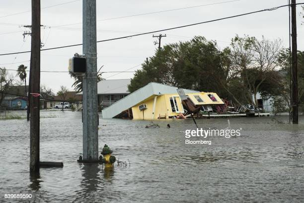 Flooding and a damaged home are seen after Hurricane Harvey hit Rockport Texas US on Saturday Aug 26 2017 As Harvey's winds die down trouble for...