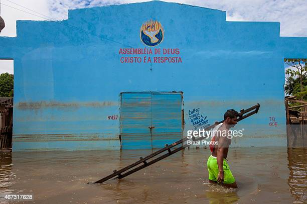 2015 flooding in Brazilian Amazon young man carries wooden staircase in front of pentecostal church building Assembleia de Deus with the words Cristo...