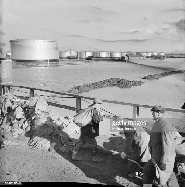Flooding on the construction site of Coryton Oil Refinery, showing flood water in the tank farm area and workmen transporting sandbags in the...