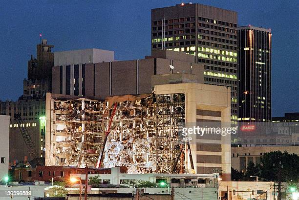 Floodlights illuminate the Albert P Murrah Federal Building in Oklahoma City 20 April 1995 as rescuers continue searching for bodies in the aftermath...