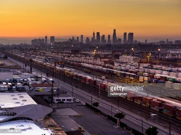 Floodlit Freight Train Yard in Vernon with Downtown LA Skyline at Sunset