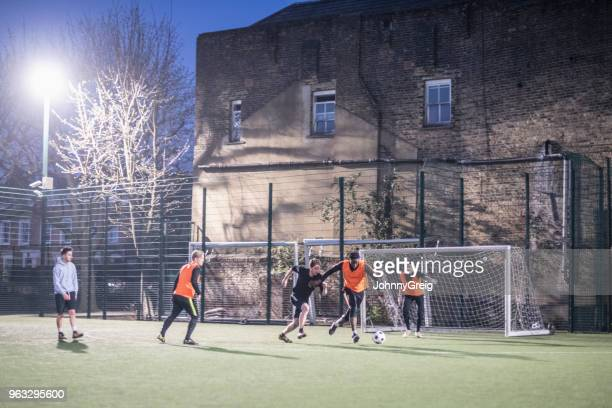 Floodlit pitch at night with group of men playing football