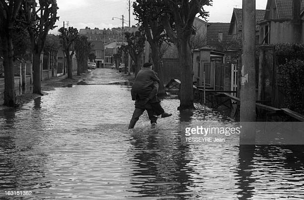 Floods Of The Seine 1959 21 janvier 1959 inondations de la Seine à VilleneuveSaintGeorges Dans une rue inondée un passant portant une personne sur...