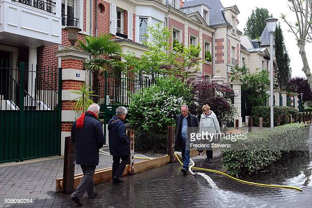 Floods the Ile de la Jatte in NeuillysurSeine near Paris some houses use sump pumps and emit streams of water on the pavement under the feet of...