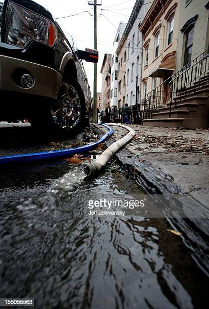 Floodwater drains from a basement as residents undertake cleanup operations on October 31 2012 in Hoboken New Jersey Known as the Mile Square City...