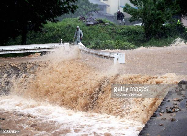 Floodwater flows as heavy rain continues on July 7 2018 in Gujo Gifu Japan 50 people are dead and at least 67 missing in heavy rains that have lashed...