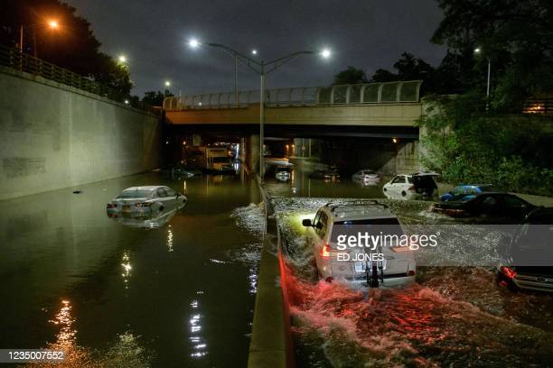 Floodwater surrounds vehicles following heavy rain on an expressway in Brooklyn, New York early on September 2 as flash flooding and record-breaking...