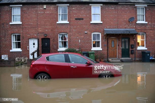 Floodwaters surrounds a car parked outside a row of houses in Shrewsbury, western England after Storm Christoph brought heavy rains and flooding...