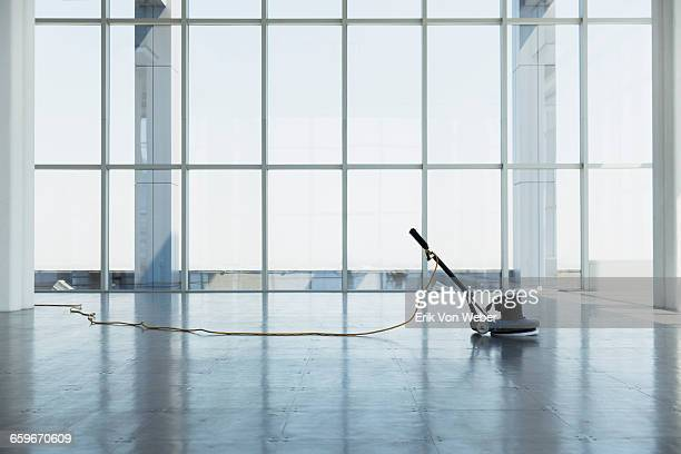 floor buffing machine in large empty office space - pulito foto e immagini stock