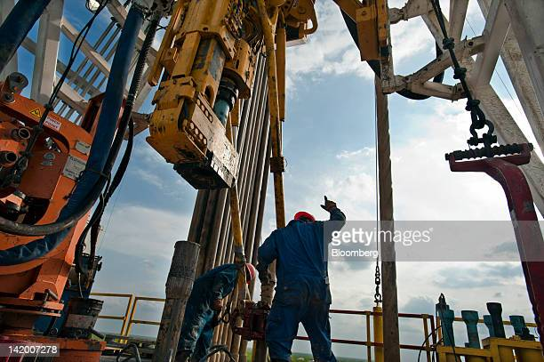 A floor hand signals to the driller to pull the pipe from the mouse hole on Orion Drilling Co's Perseus drilling rig near Encinal in Webb County...