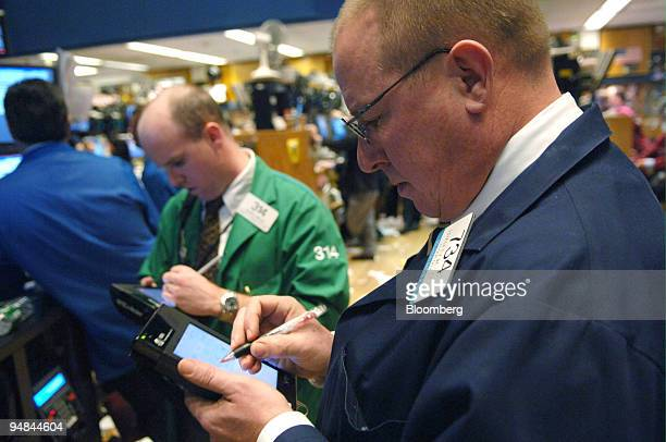 Floor Official Bradley Bailey right and Kevin Walsh work on the floor of the New York Stock Exchange Tuesday February 21 2006 US stocks declined as...
