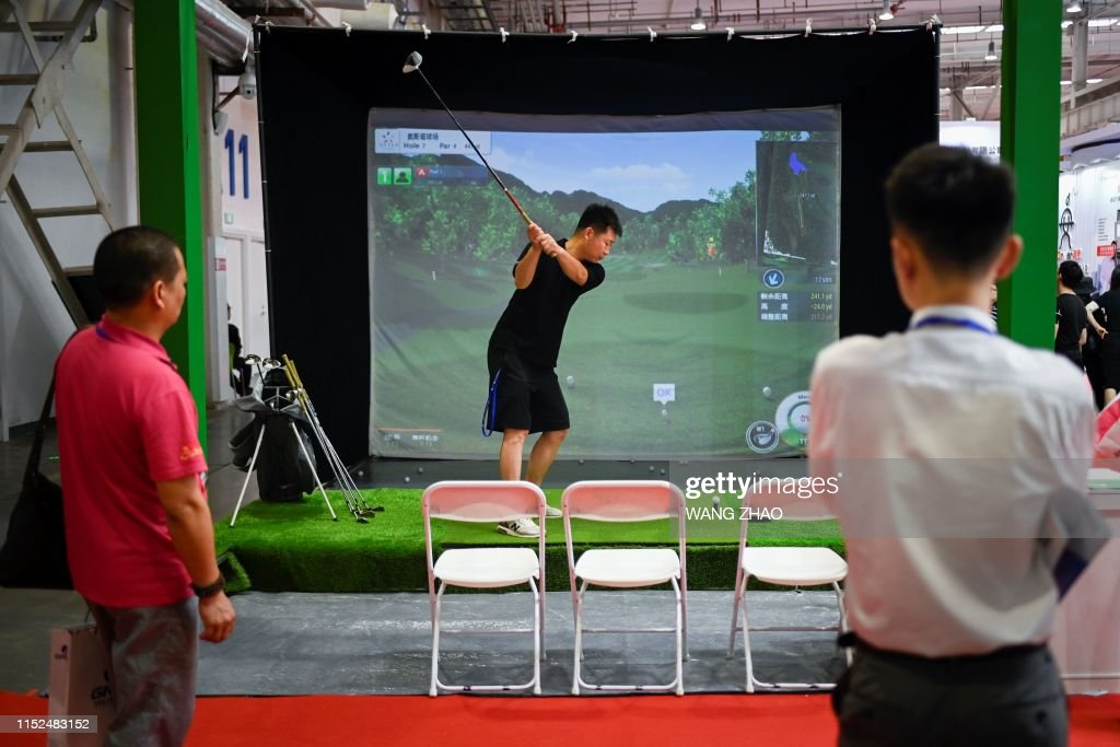 A Floor Salesman Plays Takes A Swing On A Golf Simulator At The