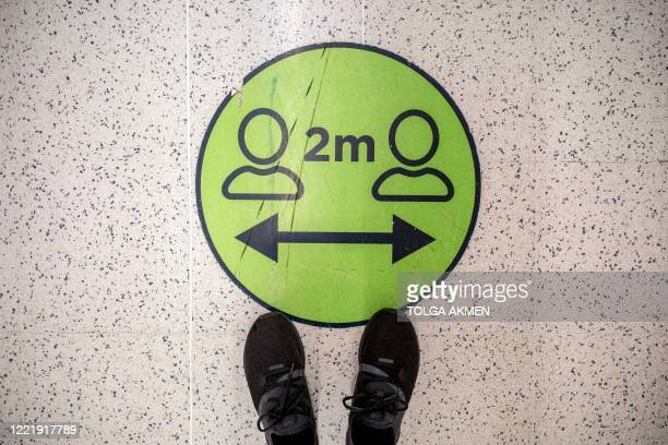 Floor sticker advising customers to maintain the British government's current social distancing guidelines and stay two metres apart, is pictured...