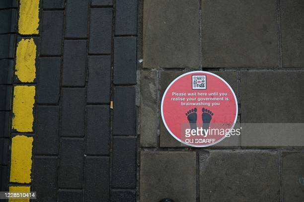 Floor sticker in the theme of a social distancing message, gives an anti-government message in Birmingham, central England on September 14, 2020...