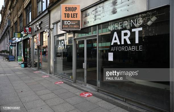 """Floor stickers asking customers to social distance due to COVID-19 are pictured on the pavement outside a closed-down shop, with a """"To Let"""" sign..."""