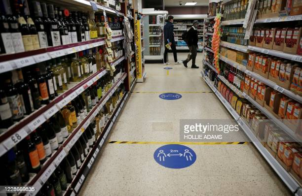 Floor stickers in the alcohol aisle inside a Tesco Metro supermarket ask customers to social distance as they shop, in London on September 23, 2020....